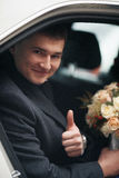 Handsome groom posing with bouquet in wedding car Royalty Free Stock Photos