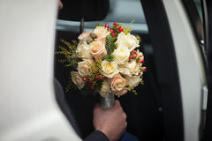 Handsome groom posing with bouquet in wedding car Stock Image