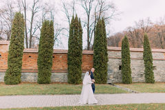 Handsome groom posing with his wife near cypress tree row and fortified wall as background in romantic park Stock Photo