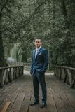Handsome groom posing and looking at camera with confidence in n. Ature Stock Images