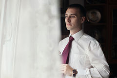 Handsome groom preparing for wedding, putting on tie near window Royalty Free Stock Image