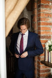 Handsome groom putting on black suit while preparing for wedding Royalty Free Stock Images