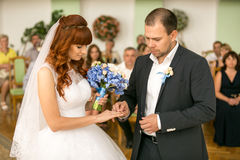 Handsome groom putting wedding ring on brides hand at registry o Stock Photography