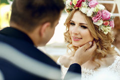 Handsome groom sensual touching emotional happy blonde bride in Royalty Free Stock Images