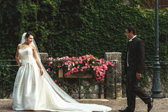 Handsome groom and sexy brunette bride walking near old wall wit Stock Photo