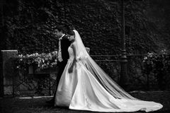 Handsome groom and sexy brunette bride walking near old wall wit Royalty Free Stock Image