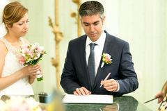 Handsome groom signing contract at wedding ceremony Stock Photography
