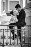 Handsome groom sitting on railing and hugging bride Royalty Free Stock Photo