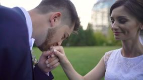 Handsome groom is softly kissing the beautiful hand of his loving smiling bride in garden. stock footage