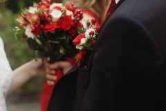 Handsome groom in stylish black suit holding wedding bouquet, wh Stock Images