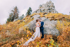 Handsome groom in stylish blue suit embracing white dressed bride holding bouquet of roses on idyllic outdoor landscape Royalty Free Stock Photography