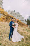 Handsome groom in stylish blue suit embracing white dressed bride holding bouquet of roses on idyllic outdoor landscape Royalty Free Stock Image