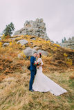 Handsome groom in stylish blue suit embracing white dressed bride holding bouquet of roses on majestic outdoor landscape Stock Photo