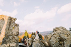 Handsome groom in stylish blue suit embracing white dressed bride on idyllic outdoor landscape with big rocks and cloudy Royalty Free Stock Images
