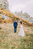 Handsome groom in stylish blue suit holding hands with white dressed bride walking on idyllic pastoral landscape. View Stock Photo