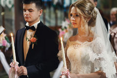 Handsome groom in suit and a beautiful blonde bride holding cand Royalty Free Stock Photography