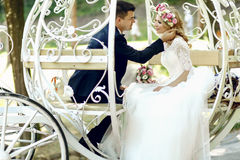 Handsome groom touching blonde beautiful bride in magical fairy. Tale carriage in sunlit park Stock Photos
