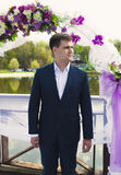 Handsome groom waiting for bride under floral arch at ceremony Royalty Free Stock Photo