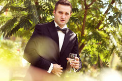 Handsome groom wedding day Smiling and drinking wine or champagne Royalty Free Stock Photography