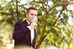 Handsome groom wedding day Smiling and drinking wine or champagne Stock Photo