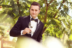 Handsome groom wedding day Smiling and drinking wine or champagne Stock Photography