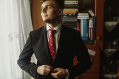 Handsome groom in white shirt with red tie buttoning up black suit, morning wedding preparation, businessman in suit looking out stock photo
