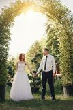 Handsome groom holds the bride`s hand near green flower archway Royalty Free Stock Photos