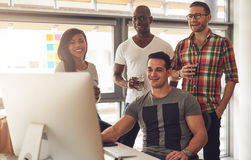 Handsome group of young adults at desk Stock Photo