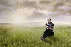 Handsome guitarist plays guitar on meadow Stock Photo