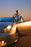 Handsome guy. Near the modern sport car at sunset time Stock Photo
