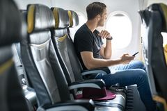 Handsome guy in airplane. Passenger sits in the airplane next to the window and holds a cellphone in the hands. He wears a black T-shirt with blue jeans. There stock photo