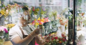 Handsome guy in apron changing open to close sign on flower shop window. Handsome guy in apron is changing open to close sign on flower shop window smiling stock video footage