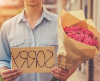Handsome Guy Asks Forgiveness from His Girlfriend. Piece of Cardboard. Bouquet of Pink Roses in Hand. Man Asks His Girlfriend to Come Back to Him. Sunny royalty free stock image