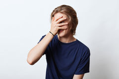 Handsome guy with attractive appearance, hiding his face with hand, looking through fingers, having shy expression. Young hipster Royalty Free Stock Images