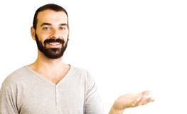 Handsome guy. With beard and gray shirt  looking in open hand on white background Royalty Free Stock Photography