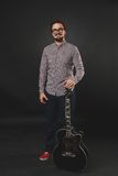 Handsome guy with beard holding acoustic guitar. Handsome guy with beard and mustache with acoustic guitar on dark background in studio Stock Photography