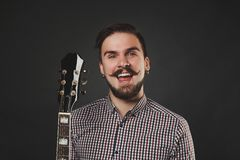 Handsome guy with beard holding acoustic guitar. Handsome guy with beard and mustache with acoustic guitar on dark background in studio Royalty Free Stock Photo