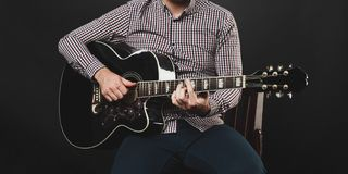 Handsome guy with beard holding acoustic guitar Stock Photography