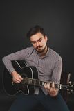 Handsome guy with beard holding acoustic guitar. Handsome guy with beard and mustache with acoustic guitar on dark background in studio Stock Images