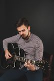 Handsome guy with beard holding acoustic guitar. Handsome guy with beard and mustache with acoustic guitar on dark background in studio Royalty Free Stock Photos