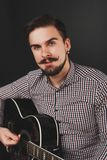 Handsome guy with beard holding acoustic guitar. Handsome guy with beard and mustache with acoustic guitar on dark background in studio Royalty Free Stock Photography