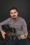 Handsome guy with beard holding acoustic guitar. Handsome guy with beard and mustache with acoustic guitar on dark background in studio Royalty Free Stock Image