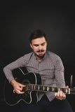 Handsome guy with beard holding acoustic guitar Stock Photo