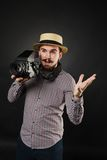 Handsome guy with beard holding vintage camera. Handsome guy with beard and mustache with vintage camera on dark background in studio Royalty Free Stock Photos