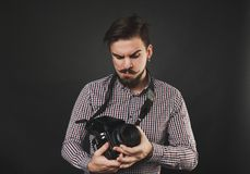 Handsome guy with beard holding vintage camera. Handsome guy with beard and mustache with vintage camera on dark background in studio Royalty Free Stock Photography