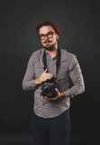 Handsome guy with beard holding vintage camera. Handsome guy with beard and mustache with vintage camera on dark background in studio Royalty Free Stock Image