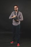 Handsome guy with beard holding vintage camera. Handsome guy with beard and mustache with vintage camera on dark background in studio Royalty Free Stock Photo