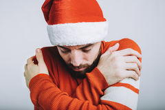 Handsome guy with beard hugging himself on white background Stock Photo