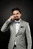 Handsome guy with beard and mustache in suit. On dark background in studio Stock Image