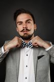 Handsome guy with beard and mustache in suit. On dark background in studio Stock Photography